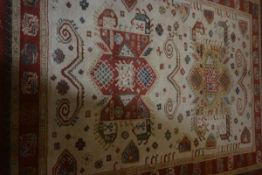 An Indian wool carpet, the central ivory field with geometric medallions flanked by geometric