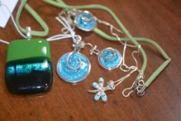 A white metal circular glass set pendant and earring set, a dragonfly pendant on chain and a glass