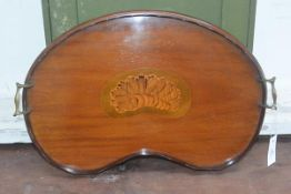 An early 20thc mahogany inlaid kidney shaped twin handled tray with brass handles, chipped
