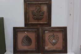 A pair of framed groups of three hardwood carved leaves,each 35.5cm x 35.5cm