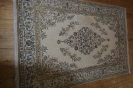 An Indian wool carpet with all over leaf and vine decoration, on ivory field with all over