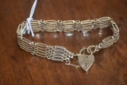 A 9ct gold gate link bracelet with padlock clasp and safety chain, 21.4g