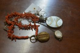 A Victorian engraved silver oval locket, a brass locket on coral necklace and a silver locket on