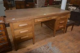 A 1930's/40's oak office desk, the plain rectangular top with single freize drawer, on two banks