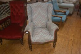 An Edwardian upholstered arm chair on turned legs with brass and china castors