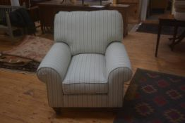 An upholstered scrolled armed armchair on circular legs