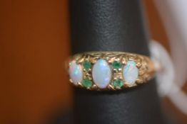A lady's opal and emerald set dress ring on 9ct gold band