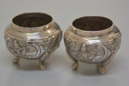 A pair of Eastern circular salt cellars, stamped 866, with seated figure chased decoration, on pad f