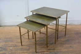 A 1950s nest of three brass coffee tables with inset gilt leather skivers on fluted tapered supports