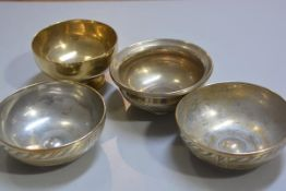 A group of Middle Eastern bronze and brass bowls with engraved decoration (d.16cm and d.14cm) (4), £