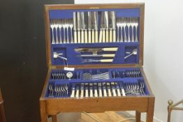 A 1920s oak table canteen, the rectangular hinged top enclosing a suite of Epns flatware including t