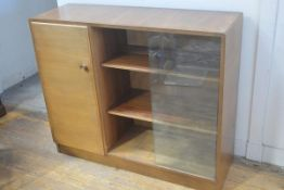 A 1950s walnut bookcase with rectangular top, fitted twin sliding glazed panels, enclosing a shelved