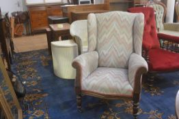 A 19thc mahogany wing chair upholstered in Hungarian style patterned woven fabric, with scroll arms,