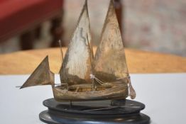 A white metal model of an Arab dhow, complete with hardwood stand, sails etc. (h. 20cm including sta