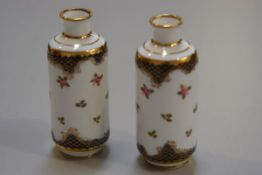 A pair of Crown Staffordshire miniature cylinder vases decorated with roses and gilt blue reserves (