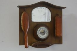 A 1920s/30s walnut hall mirror with aneroid barometer, mounted with three various clothes brushes (h