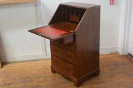 A lady's reproduction mahogany writing bureau, the top with fall front enclosing a fitted interior,