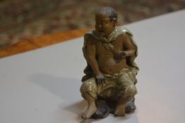 A Chinese mud glazed figure of a monk seated on a tree root (h.14cm), losses to fingers and toes, £2