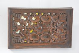 An Eastern rectangular carved mirror panel back panel with flower and stylised leaf design (35cm x 5