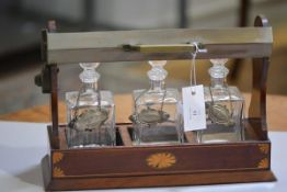 An Edwardian mahogany inlaid three division tantallus complete with three replacement bottles with w
