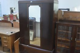 A 1920s mahogany wardrobe, the moulded cornice above a shaped inset mirror panel door above a single