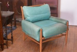 A modern teak framed turquoise leather vintage 1970s style easy chair retailed by Anthropologie, on