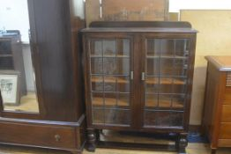 A 1920s oak ledgeback bookcase, the top with moulded edge above a pair of twin leaded glass panel do