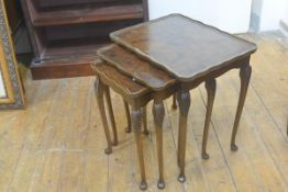 A figured walnut nest of three coffee tables, the tops with scalloped borders, raised on carved moul