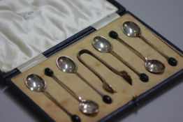 A set of six Sheffield silver bean handled coffee spoons, complete with tongs, in original fitted Ma