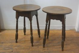 A pair of oak turned wood occasional tables with circular tops and shaped aprons on splay tapered ba