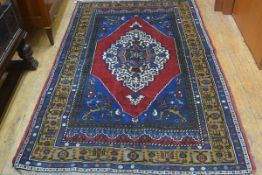 A handknotted Turkoman rug, the centre medallion enclosed within a multiple flowerhead and leaf bord