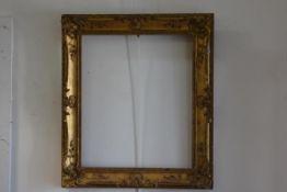 A 19thc rococco style gilt composition frame (exterior: 83cm x 73cm. Interior 62cm x 52cm) (losses)