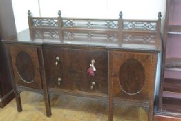 A late 19thc Chippendale style ledgeback sideboard with pierced gallery back, mounted with finials