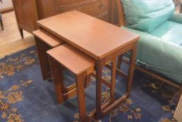 A G Plan style teak nest of three coffee tables, the larger with foldover swivel top, with twin pull