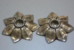 A pair of white metal candlestick holders in Scandinavian style, in the form of open flowers, unmark