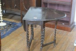 An oak oval drop leaf gateleg tea table, the top with moulded edge, raised on barley twist supports