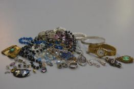 A bag containing a collection of costume jewellery including a paste pearl necklace, a crystal bead