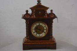 A Victorian oak mantle clock with pedimented top, above a circular enamelled dial, with roman numera