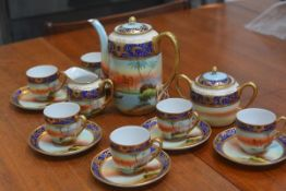 A Japanese 1920s/30s fifteen piece coffee set decorated with Noritake style landscape panels, with g