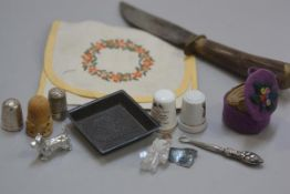 A horn handled knife, an embroidered 1930s handkerchief case, two china thimbles, two silver thimble