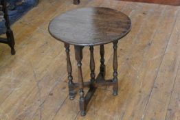 A 1920s oak circular occasional table with flip top, raised on folding turned baluster supports (h.