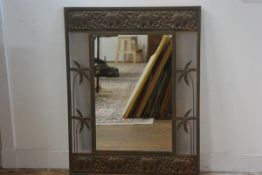 An anodised copper finish rectangular wall mirror with relief carved elephant frieze, with palm tree