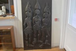An African hardwood two section relief carved panel depicting three female figures carrying water go