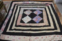 A 1920s reversable black cotton and floral and rose pattern fabric patchwork quilt, the centre with