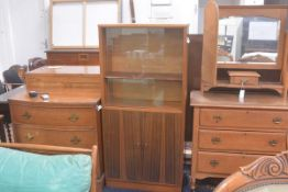 A 1970s walnut upright twin sliding glazed door and twin panel door bookcase with adjustable shelves