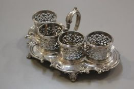 An Edwardian Sheffield plated four section pierced cup holder serving dish with C scroll border