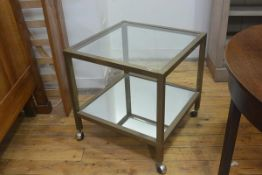 A 1970s brass two tier lamp table with inset glass panel and mirror panel to base, on square