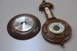 An Edwardian walnut circular aneroid wall barometer complete with thermometer, with carved border