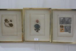 A set of three gilt box frames enclosing linen panels with applied artefacts such as enamelled