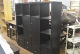 An Ikea modular black ash storage unit fitted four open sections to top with an arrangement of